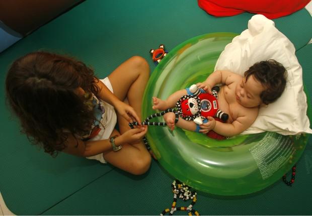 Um bebê de pele branca com síndrome de Down está deitado no centro de uma boa de piscina em forma de rosca. Ele está apoiado em um travesseiro e segura um bichinho de pelúcia. Uma garota morena sentada à frente do bebê segura uma corda e puxa o pé dele para fazer exercícios de estimulação precoce.