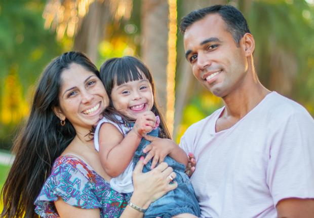 Mulher e homem abraçam menina pequena com síndrome de Down. Todos sorriem. Crédito da foto: Su Florentino