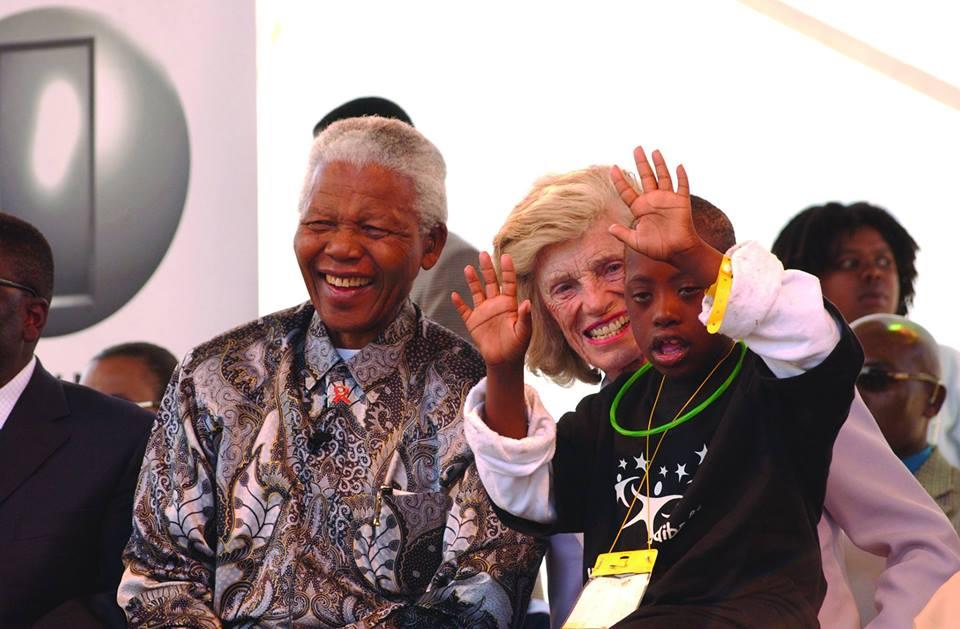 Mandela com Eunice Schriver e um menino negro com sindrome de Down, acenando.