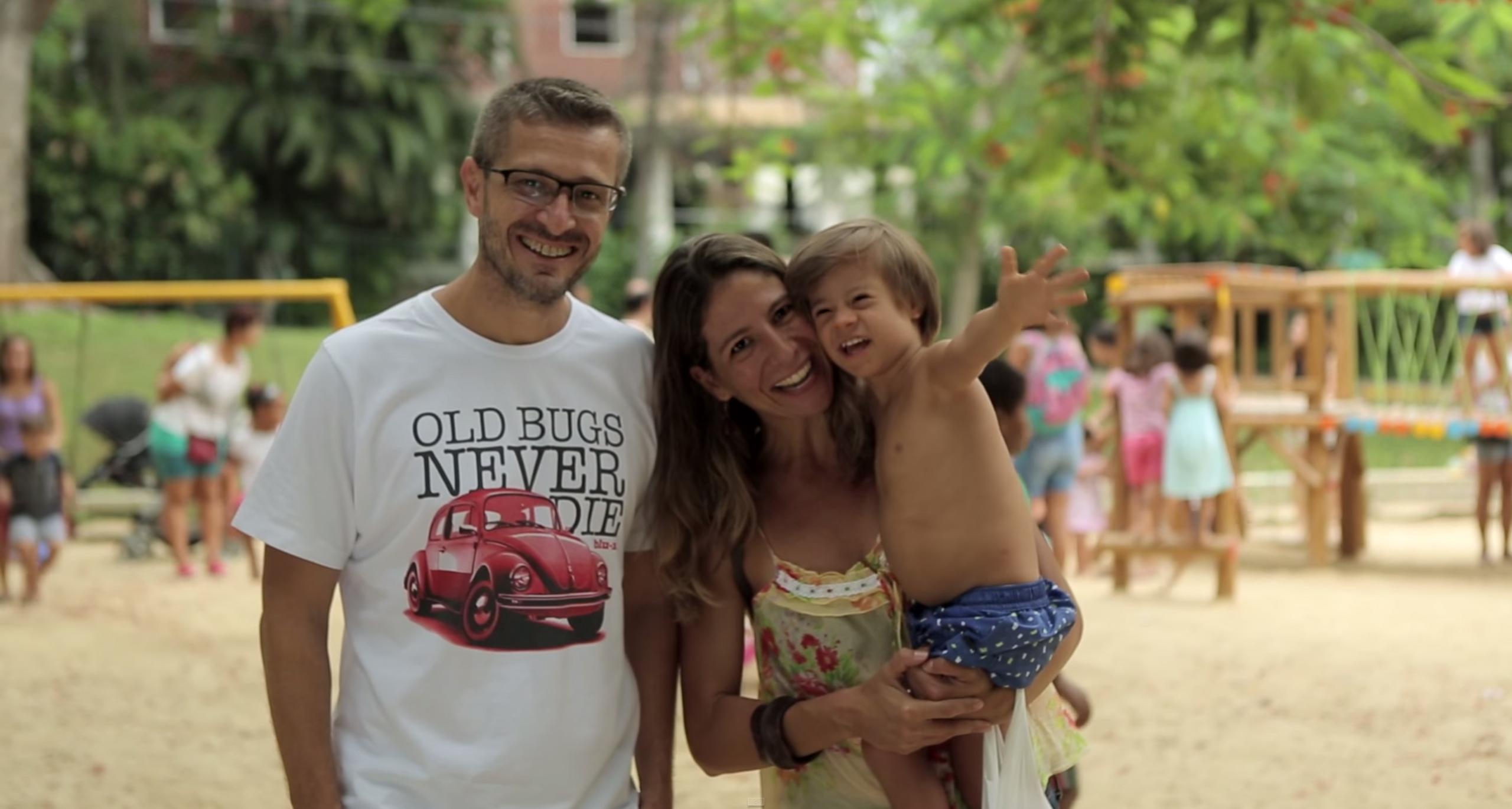 Pai, mãe e filho com síndrome de Down posam para a foto. A mãe segura o filho no colo enquanto ele acena para a câmera..