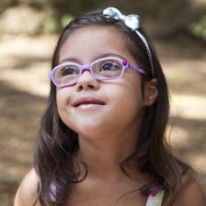 Garota com síndrome de Down e óculos ilustra a capa da Cartilha sobre Problemas de Visão.