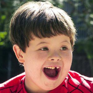 Garoto com síndrome de Down ilustra a capa da Cartilha sobre Cuidados com a Saúde Bucal.