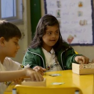Garota com síndrome de Down está na escola estudando no episódio de Qual é a diferença?