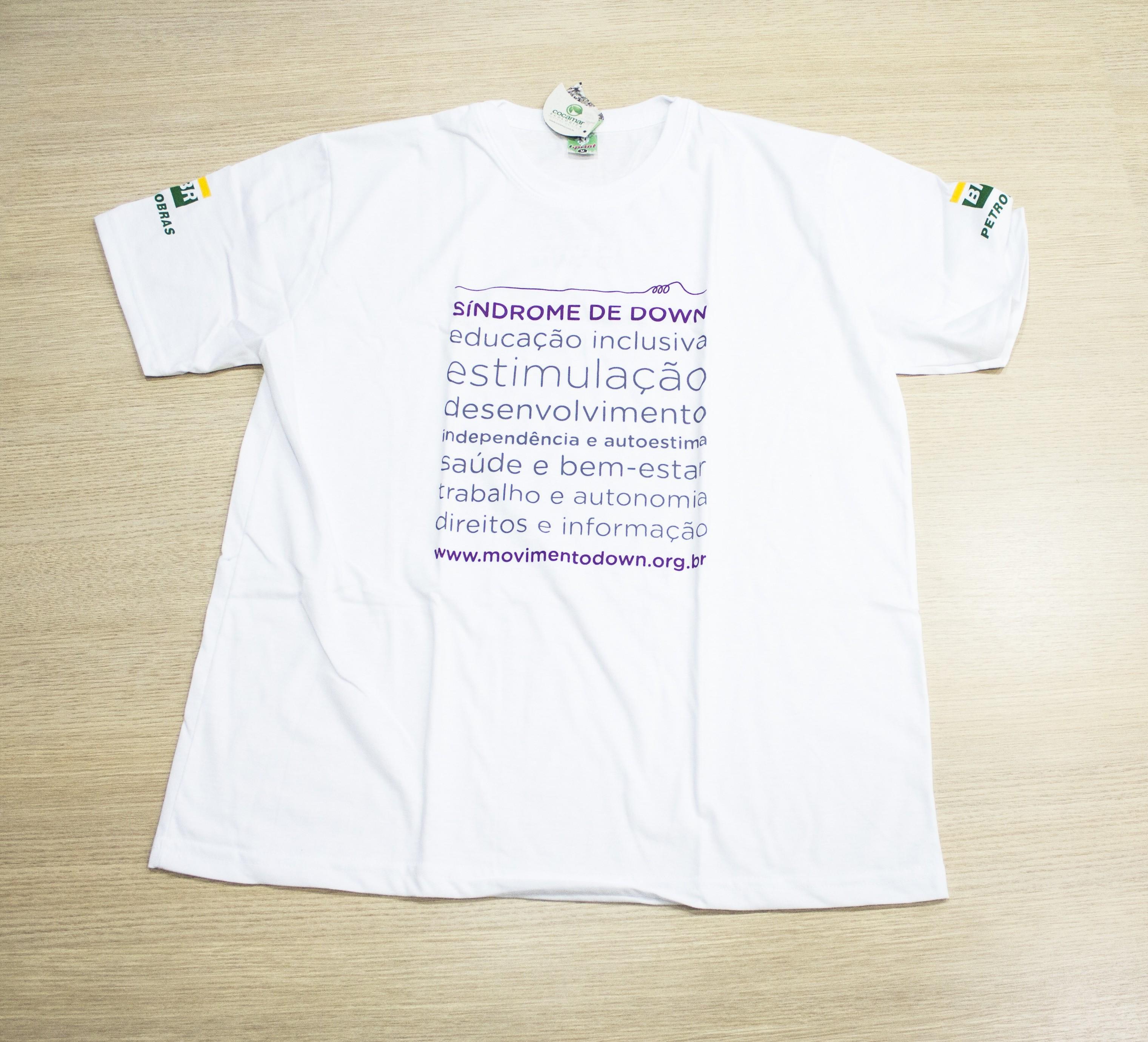 Camisa branca em malha ecológica com estampa de termos relacionados á inclusão e ao desenvolvimento.