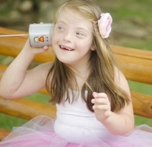 Garota com síndrome de Down ilustra a capa da Cartilha sobre Problemas da Audição.