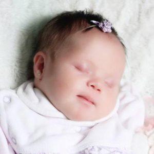 Bebê com síndrome de Down dormindo ilustra a capa da Cartilha sobre Problemas do Sono.