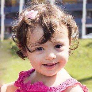 Bebê com síndrome de Down ilustra a capa da Cartilha sobre Espasmos Epiléticos.