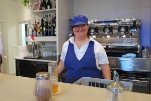 Funcionária do Milleluci Café com síndrome de Down aparece vestida com seu uniforme de trabalho e em frente à máquina de café. Ela sorri e aparece feliz em estar ali.