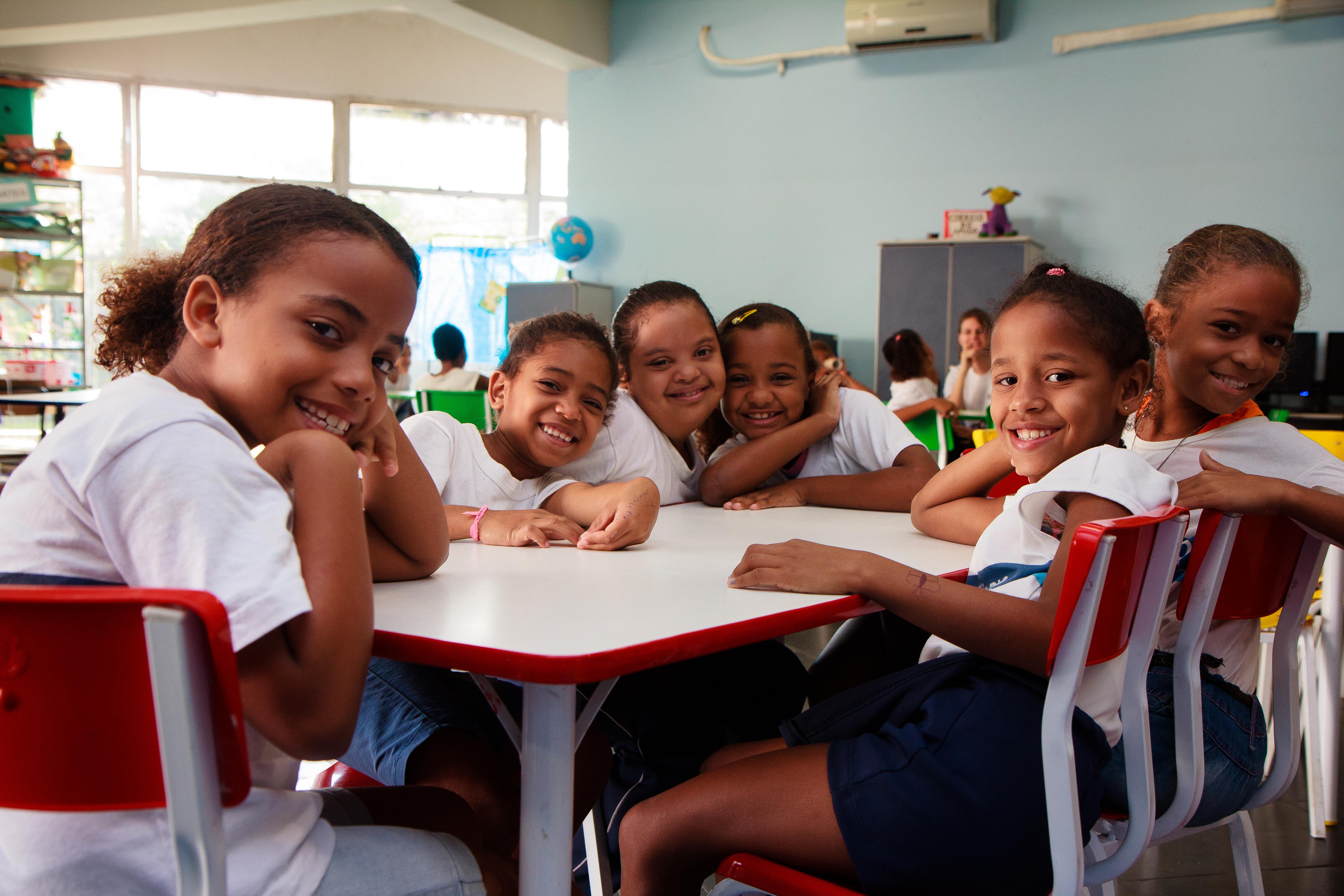 Cinco garotas estão sentadas em carteiras em uma sala de aula. Todas usam uniforme de escola. A aluna do meio tem síndrome de Down, enquanto as outras quatro que estão ao redor não apresentam nenhuma deficiência. A foto é a capa da cartilha Escola para Todos.
