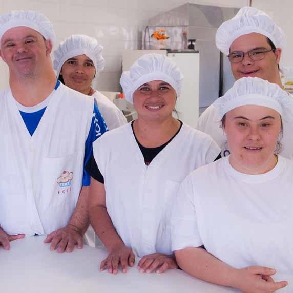 Um grupo de jovens com e sem síndrome de Down posa para a foto em seu local de trabalho. Eles usam um uniforme branco e uma touca branca na cabeça. Todos sorriem. A imagem exemplifica a importância da autonomia e inclusão social de pessoas com deficiência.