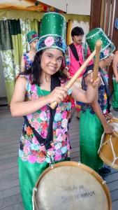 Priscilla tem síndrome de Down e é professora de pilates, ginástica e zumba. Na foto ela aparece tocando maracatu vestida com roupa e chapéu coloridos. Ela está bem feliz.
