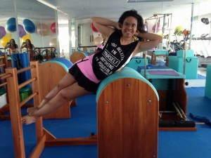 Priscilla tem síndrome de Down e é professora de pilates, ginástica e zumba. Na foto ela aparece fazendo um dos exercícios de pilates em uma máquina no estúdio de pilates.