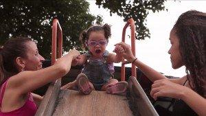 Manu é uma criança com síndrome de Down. Na foto, ela aparece em cima de um escorregador, se preparando para escorregar. A irmã está do lado direito da foto e a mãe do lado esquerdo. Cada uma segura uma mão da Manu para ajudá-la a escorregar.