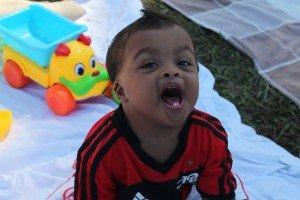 Bebê negro com síndrome de Down. Ele está em cima de uma toalha de piquenique com alguns brinquedos em volta e abre a boca tentando falar. Essa imagem ilustra o exercício de estimular a fala.
