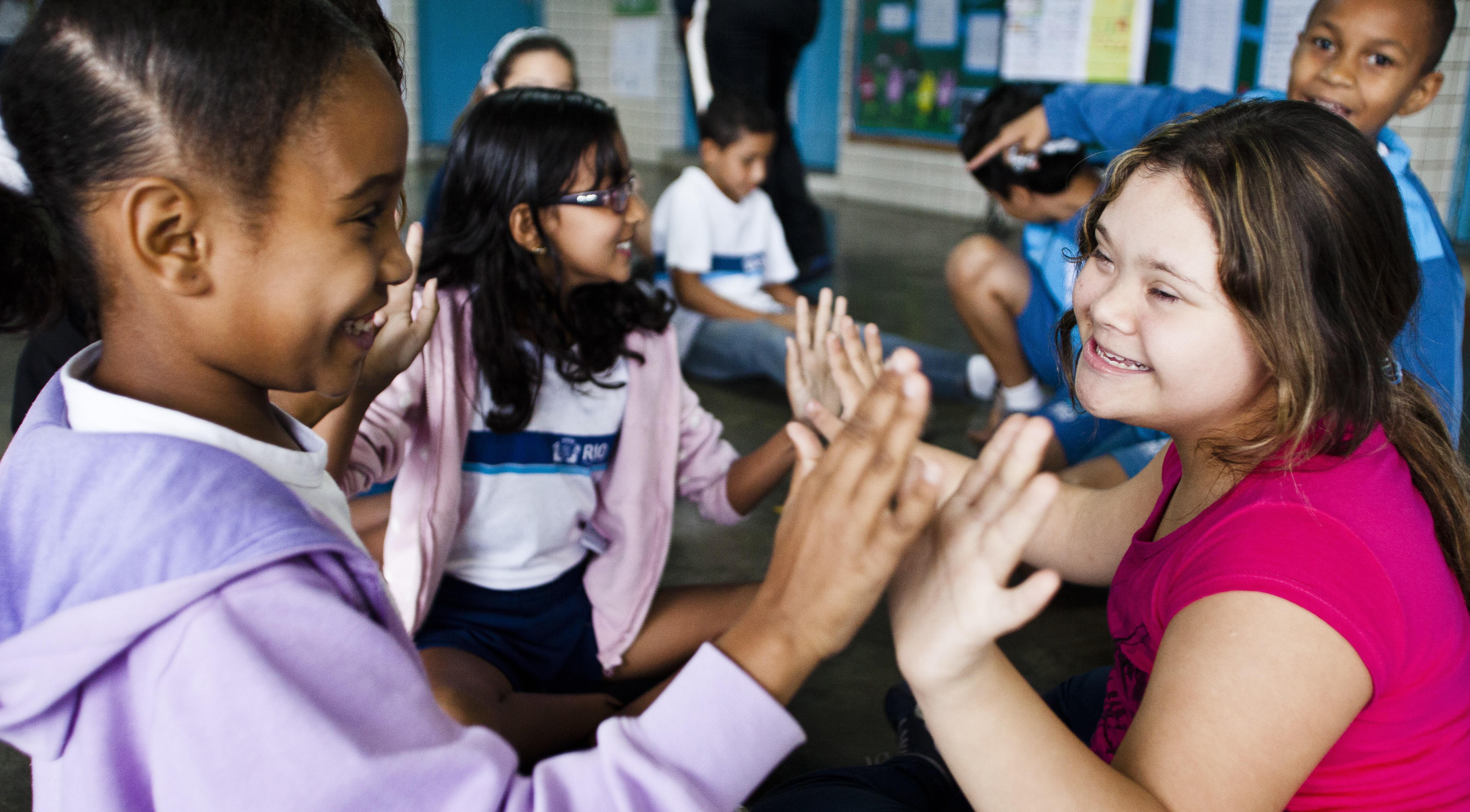 Imagem ilustra uma sala de aula inclusiva. Na foto podemos ver em primeiro plano uma garota negra sem deficiência brincando com uma garota branca com síndrome de Down. Uma sorri para a outra. Na mesma sala de aula, outras crianças sem nenhuma deficiência aparente também brincam umas com as outras. Elas estão usando o uniforme da escola municipal do Rio de Janeiro.