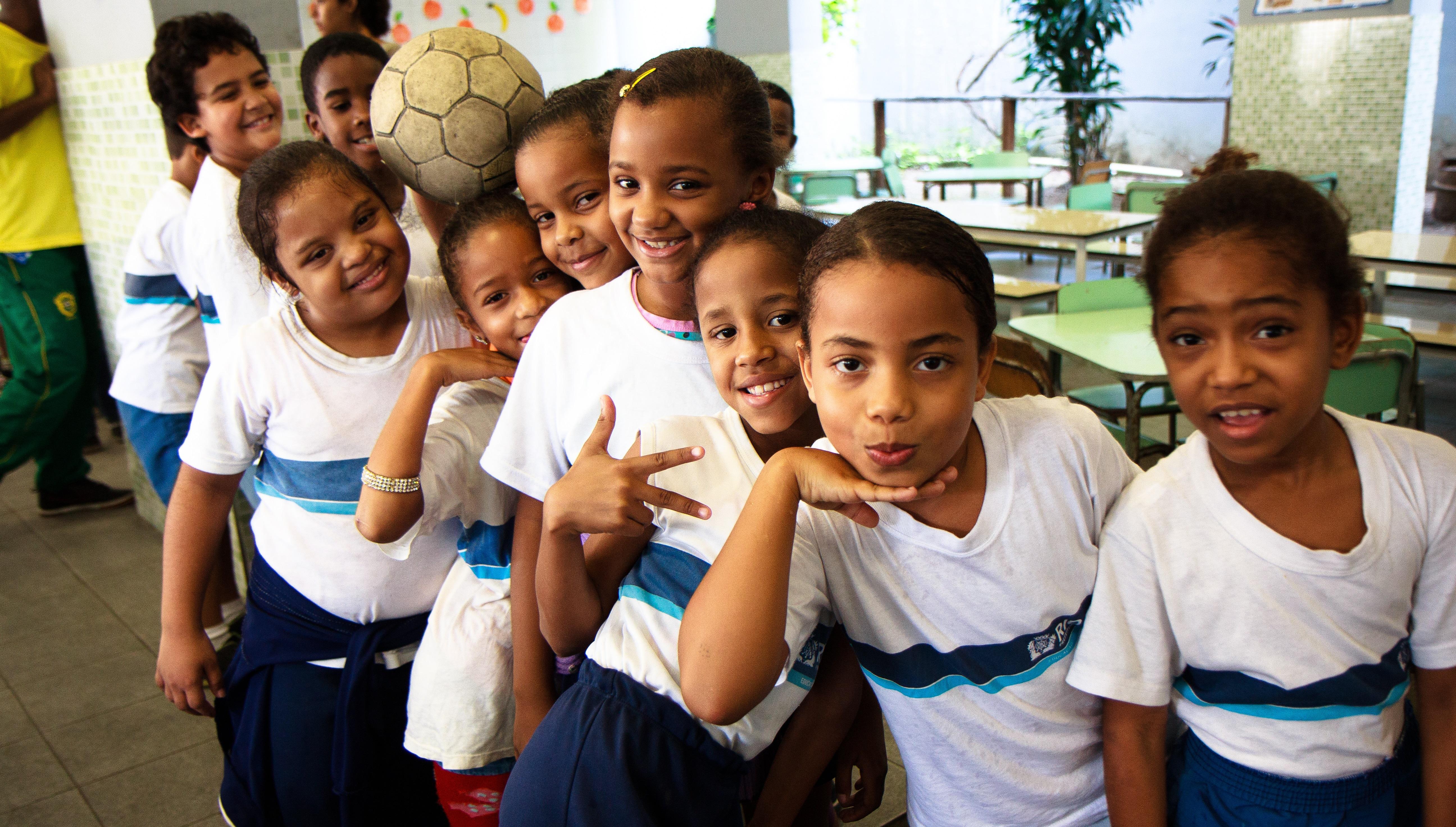 Várias garotas aparecem na imagem. Elas estão em fila, usam o uniforme da escola e fazem pose para a foto. Quase todas as meninas não têm deficiência, apenas uma tem síndrome de Down, mostrando que ela tem os mesmos direitos à educação que as demais.