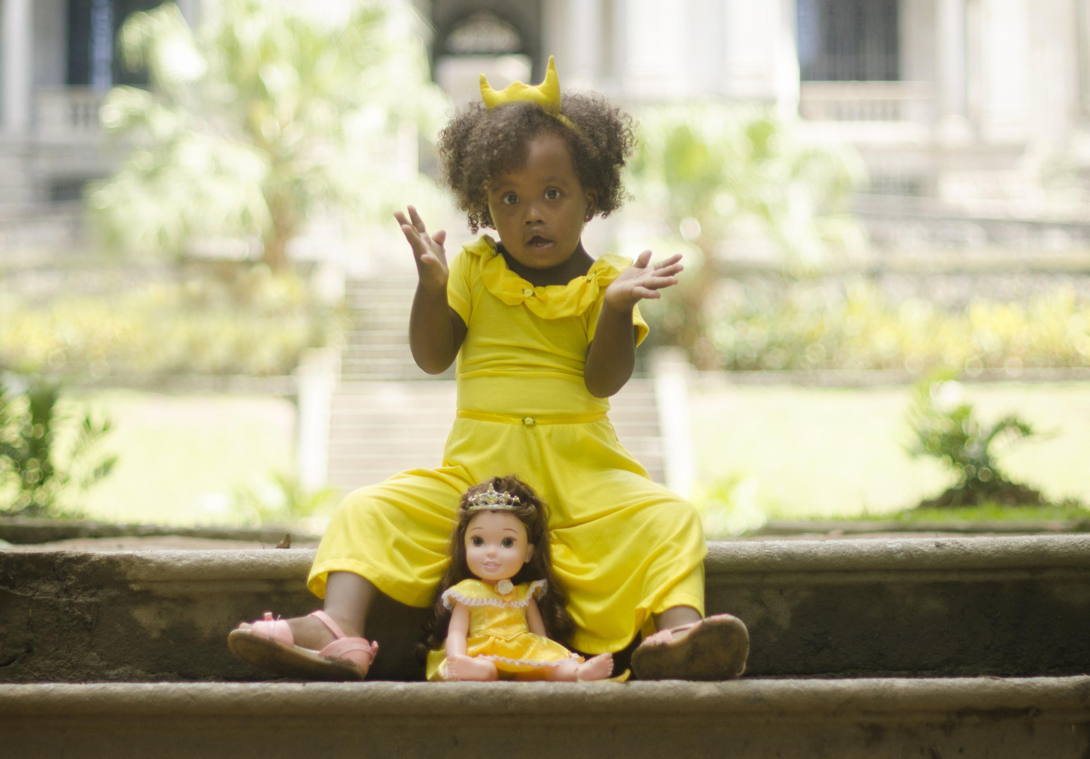 Garota negra com síndrome de Down. Ela levanta os braços como se estivesse fazendo uma pergunta.