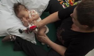 Um bebê com síndrome de Down faz exercícios para estimular a sua coordenação motora. Ele está deitado em um travesseiro e segura um bichinho de pelúcia. Uma mulher sentada no chão e na frente do bebê segura o sei corpo de lado para ajudá-lo nos exercícios de estimulação.