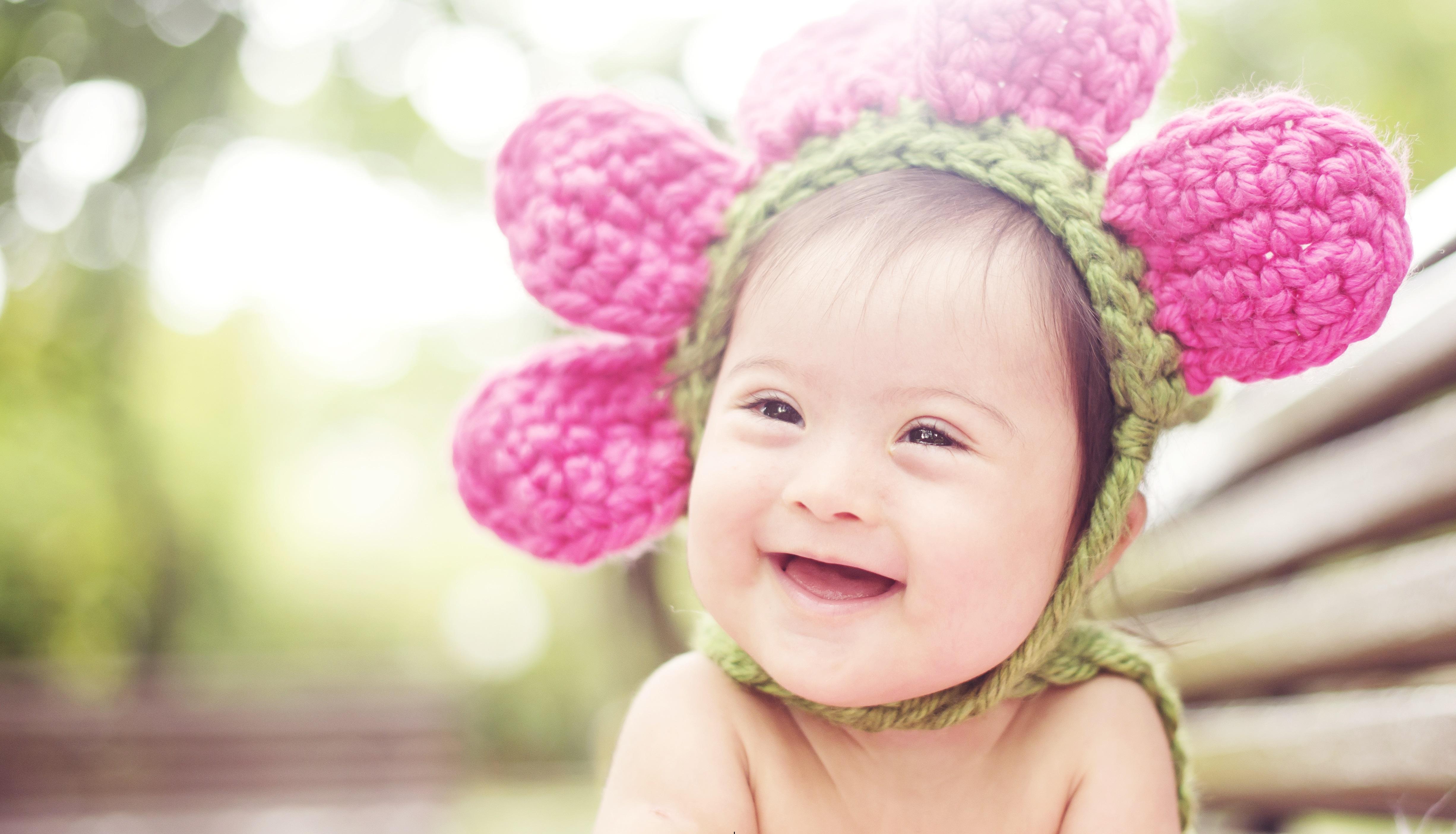 Um bebê com síndrome de Down ri para a foto. Ele está muito feliz. Ele usa um chapéu em forma de flor na cabeça.