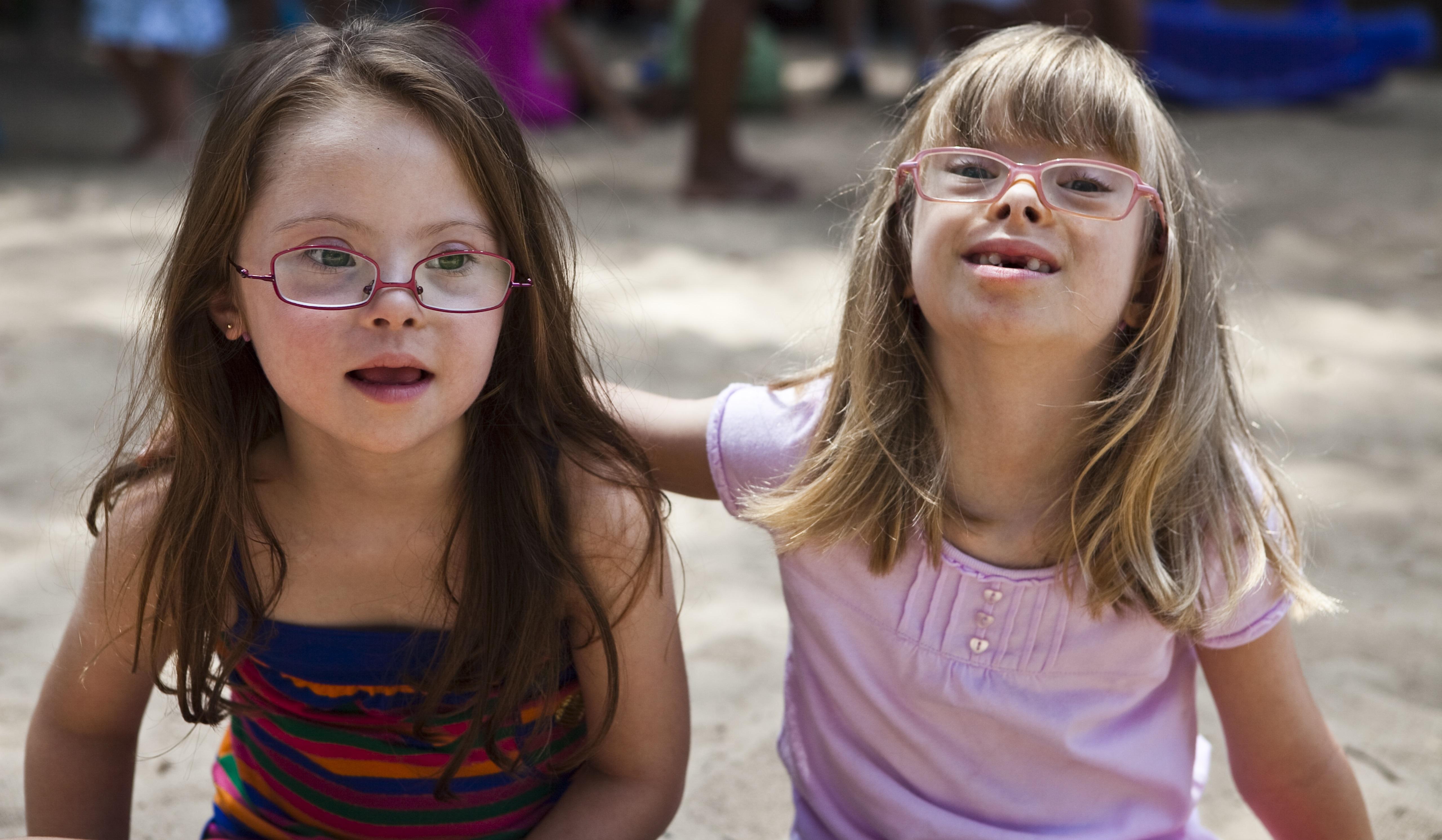 Duas garotas com síndrome de Down estão sentadas de frente para a foto. A que está do lado esquerdo olha levemente para o lado, enquanto a que está do lado direito olha para frente e apoia o braço nas costas da amiga.