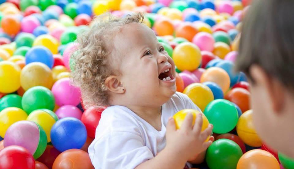 Criança com síndrome de Down se divertindo em uma piscina de bolinhas durante a CaminhaDown de Brasília - DF de 2015.