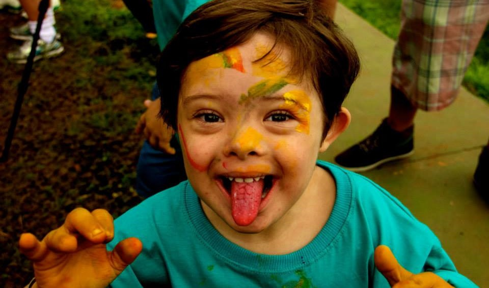 Garoto com síndrome de Down durante a 1ª CaminhaDown São Paulo. Ele está fazendo uma atividade de pintar e mostra o rosto e as mãos cheios de tinta. Ele se diverte dando a língua para a fotógrafa.