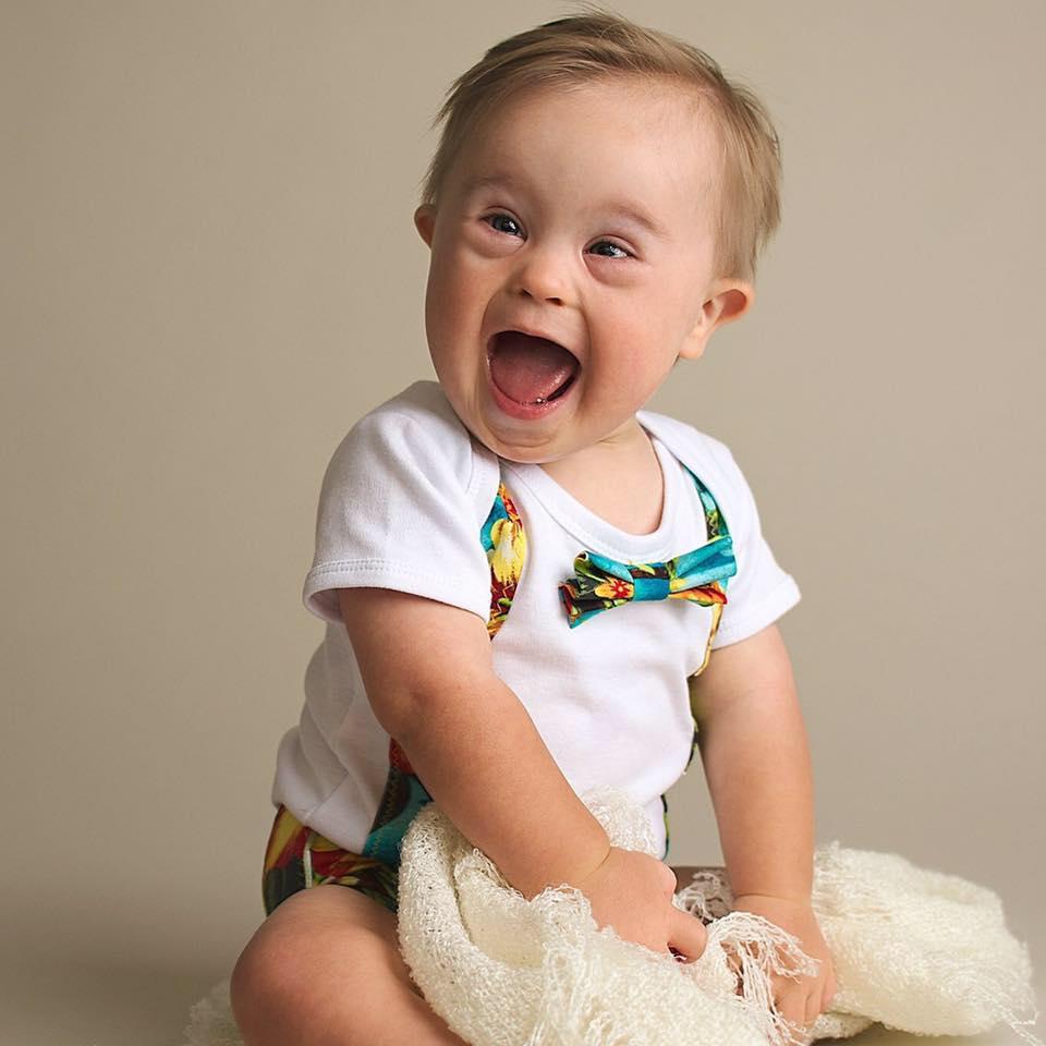 bebe com sindrome de down, sentado no chao com um enorme sorriso.