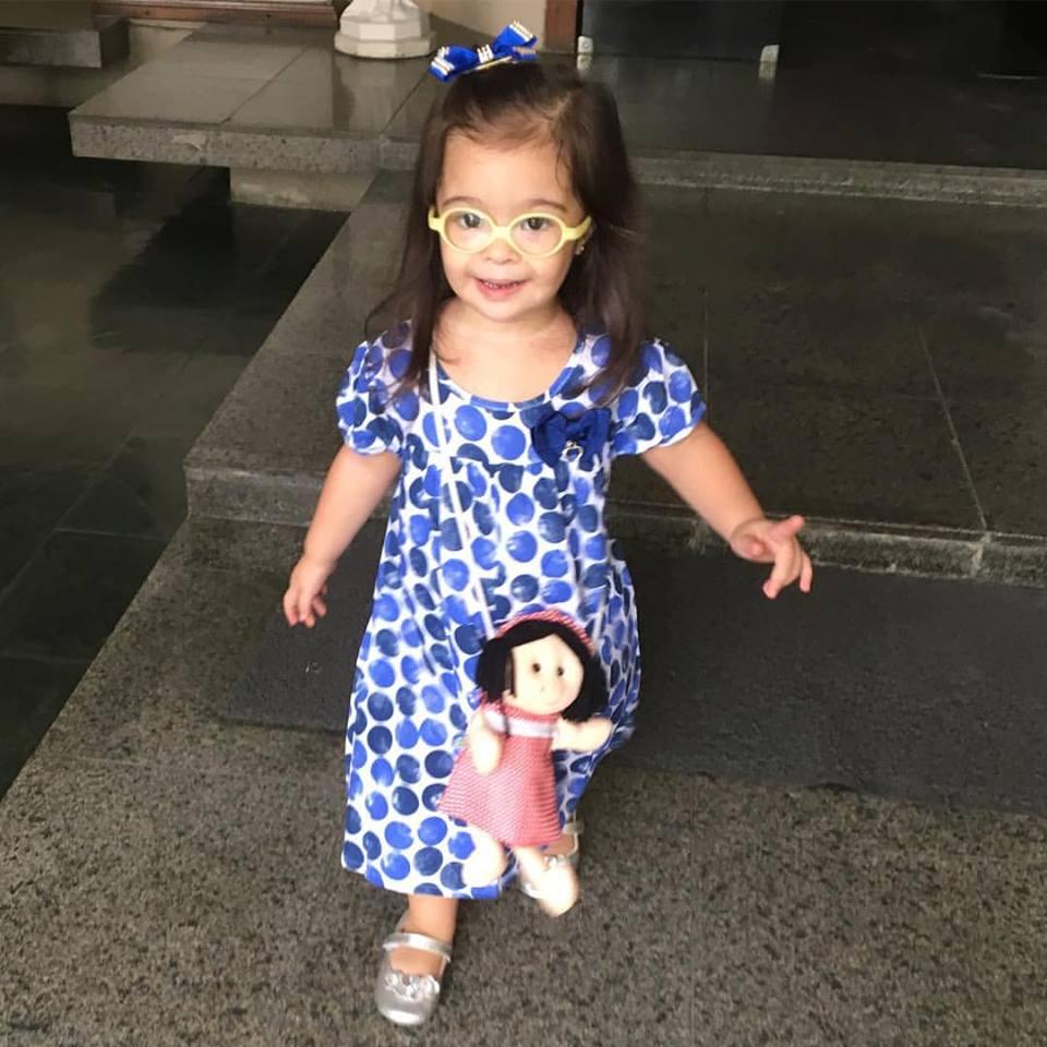 Luisa, de oculos, vestido branco com bolotas azuis e bolsa de boneca.