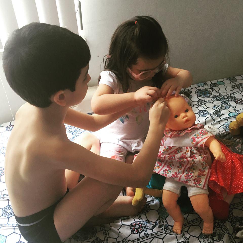 menina e menino penteiam cabelo de boneca.