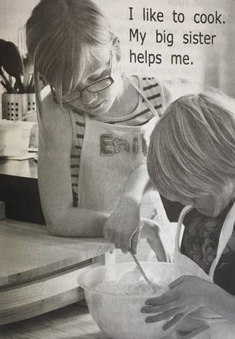 foto de duas meninas fazendo bolo e texto curto.