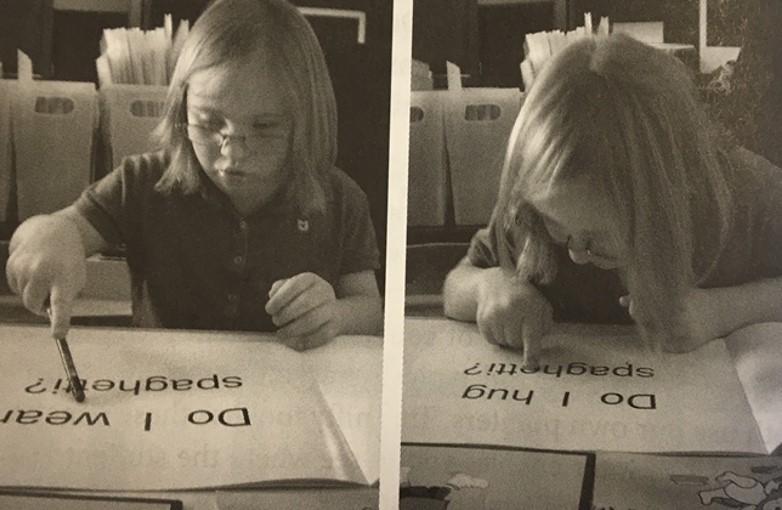 menina lendo o livro acompanhando o texto com ponta do lapis e ao lado acompanhando com o dedo , debrucada sobre o livro.