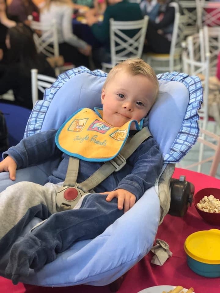 bebe no bebê conforto com macacão azul e babador..