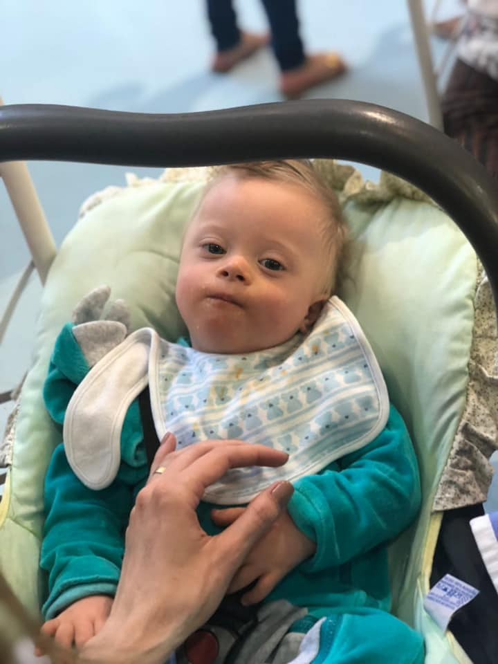 bebe no bebê conforto com macacão verde e babador..