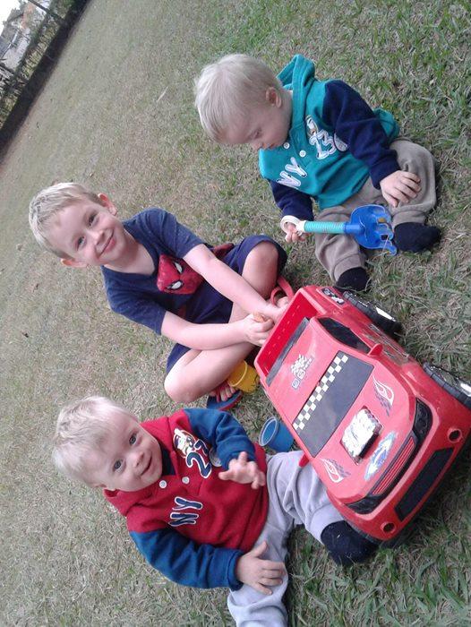 dois bebes e um menino sentados na grama, brincando com um carro de brinquedo grande.