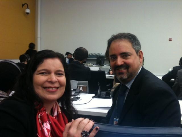 mulher e homem, sorrindo, em sala de conferencias.