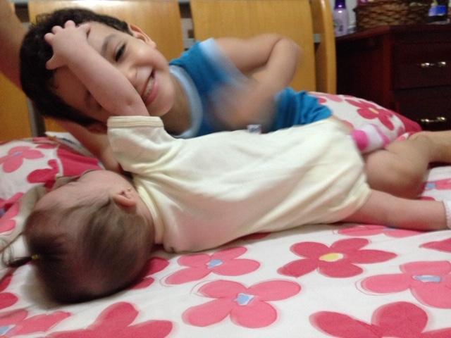 bebê brinca com menino na cama.