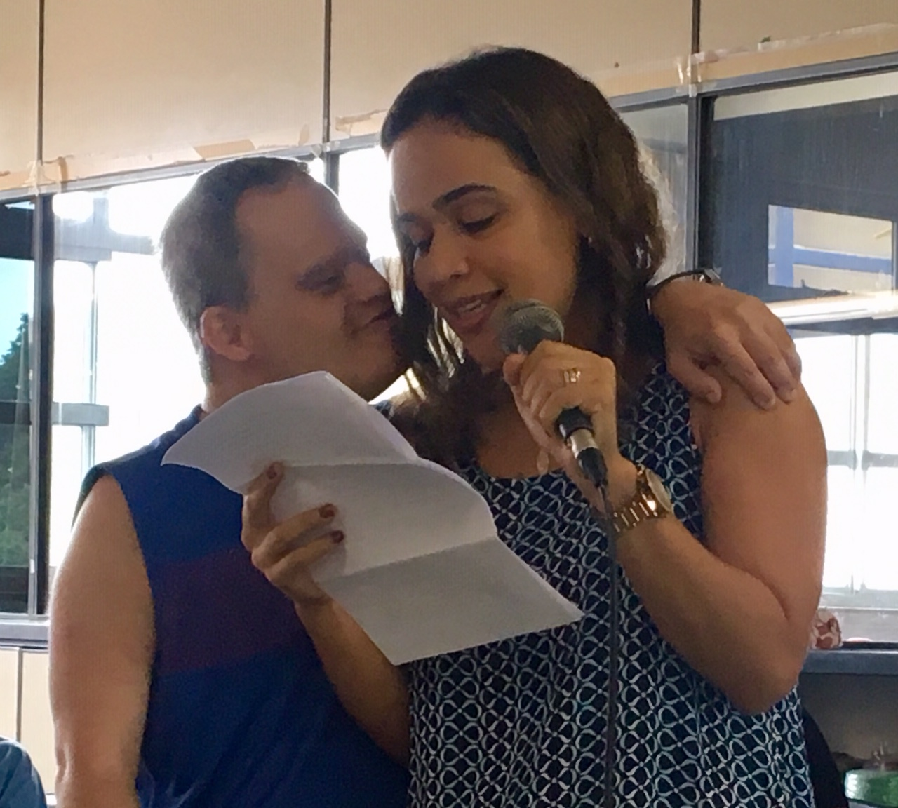 mulher com microfone le texto ao microfone, enquanto homem tem o braco em volta de seus ombros.