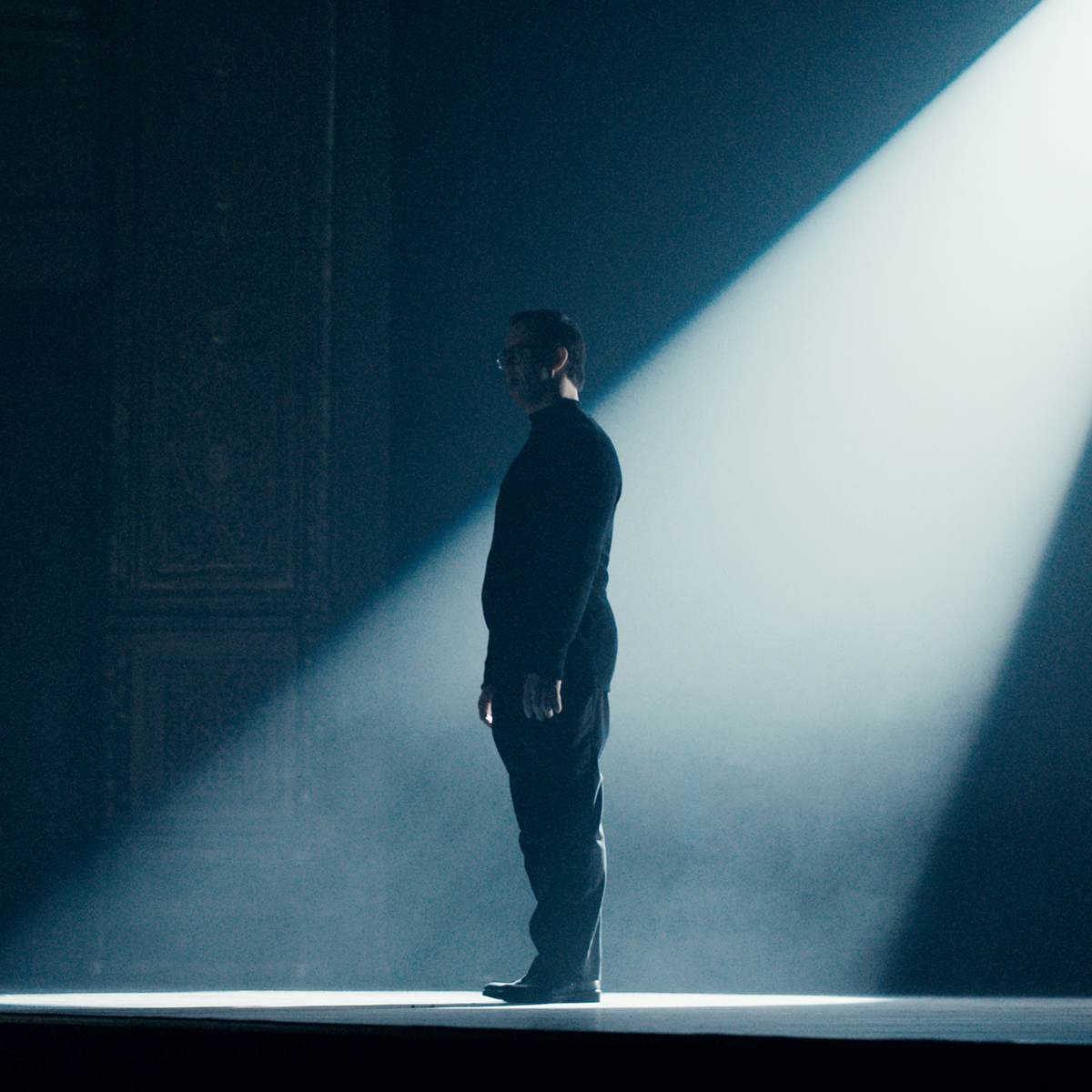 homem em pé em palco escuro, com luz sobre ele.