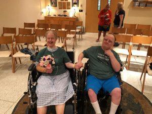 homem e hulher em cadeira de rodas em capela. ela com flores na mao.