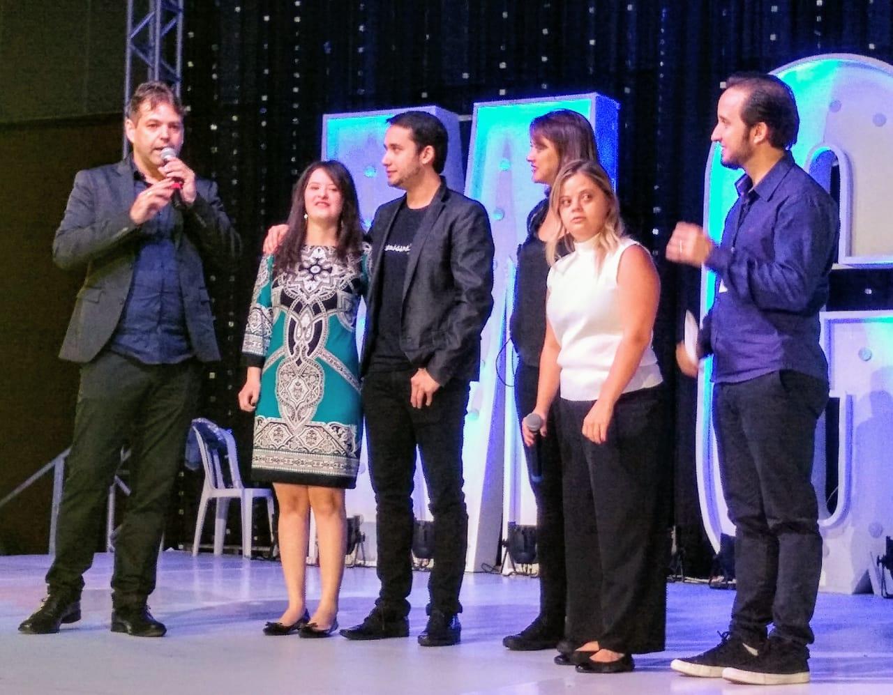 Em palco, homem fala ao microfone ao lado de outros dois homens e três mulheres.