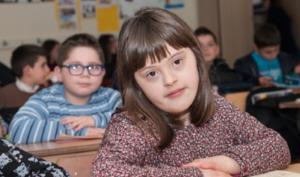 foto de menina numa sala de aula com estudantes em volta.