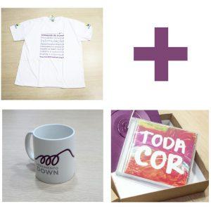 Caixa contendo: CD Toda Cor, Caneca branca de porcelana com a marca do Movimento Down e Camisa Ecológica branca com termos relacionados à inclusão e ao apoio ao desenvolvimento.