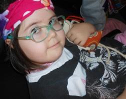 Giovanna Bignami Grecchi é filha de Rosana Bignami. Ela é uma criança de 10 anos e tem síndrome de Down. Na foto, usada para ilustrar o texto sobre inclusão, Giovanna sorri para a câmera e segura uma boneca.