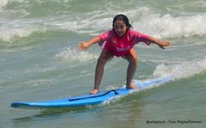 Letícia tem síndrome de Down. Na foto, ela aparece surfando em uma prancha azul no mar. Em pé, Letícia se equilibra para surfar na onda. Com o surf, ela aprendeu que pode superar qualquer desafio.